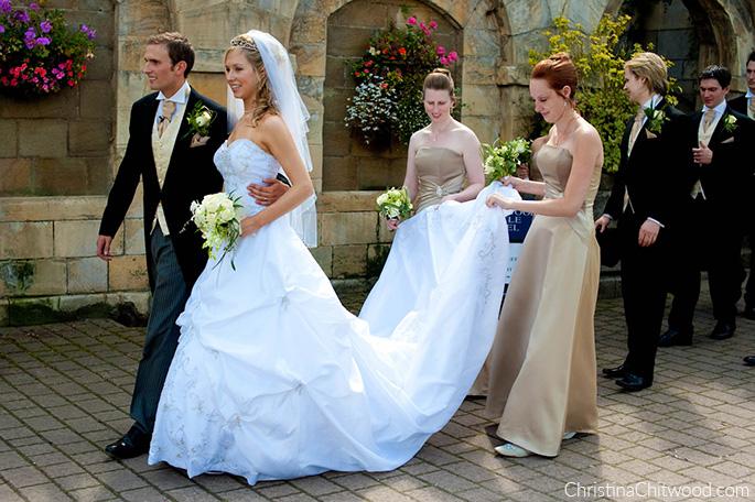 Christina, Tom, Groomsmen, and Bridesmaids Holding Christina's Train