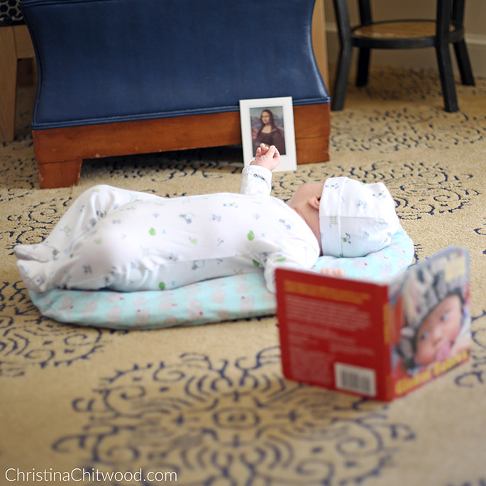 Our Baby Boy Enjoying Concentrating on the Mona Lisa Art Postcard in His Montessori Space on His Second Trip at 2 Months Old