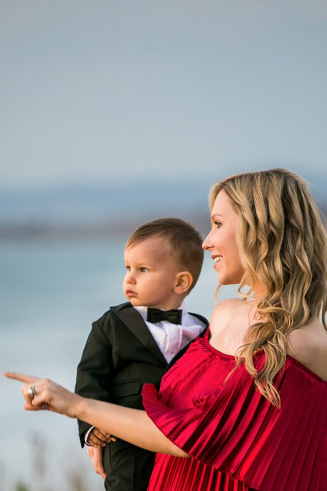 Fashion blogger, Christina Chitwood, holding her toddler son and pointing at the sky. Womens Fashion Amazon Maxi Dress, Circus by Sam Edleman Booties, Nadri Earrings. Boys Hope and Henry Tuxedo