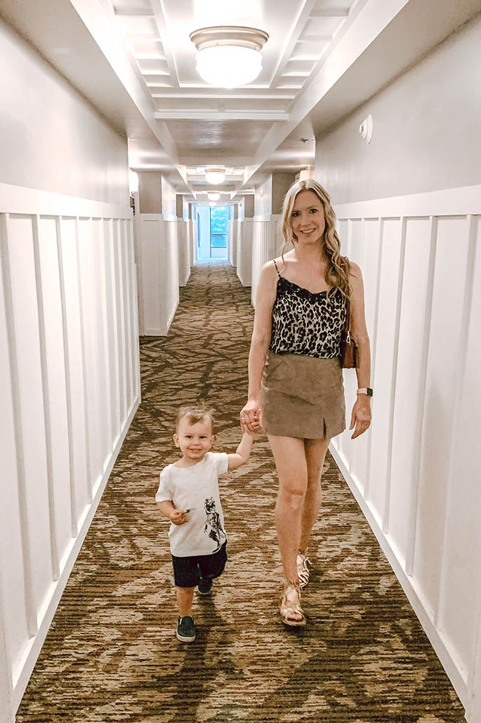 Fashion blogger, Christina Chitwood, holding her toddler son's hand walking down a Kauai, Hawaii resort hallway. She's wearing a BP. camisole, a BLANKNYC mini skirt, and a Steve Madden handbag.