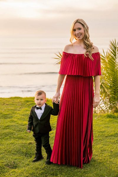Fashion blogger, Christina Chitwood, in a maxi dress holding hands with her toddler son. Womens Fashion Amazon Maxi Dress, Circus by Sam Edleman Booties, Nadri Earrings. Boys Hope and Henry Tuxedo