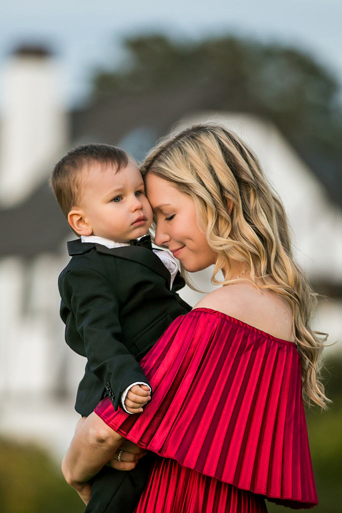 Fashion blogger, Christina Chitwood, in a metallic red maxi holding her toddler son. Womens Fashion Amazon Maxi Dress, Circus by Sam Edleman Booties, Nadri Earrings. Boys Hope and Henry Tuxedo
