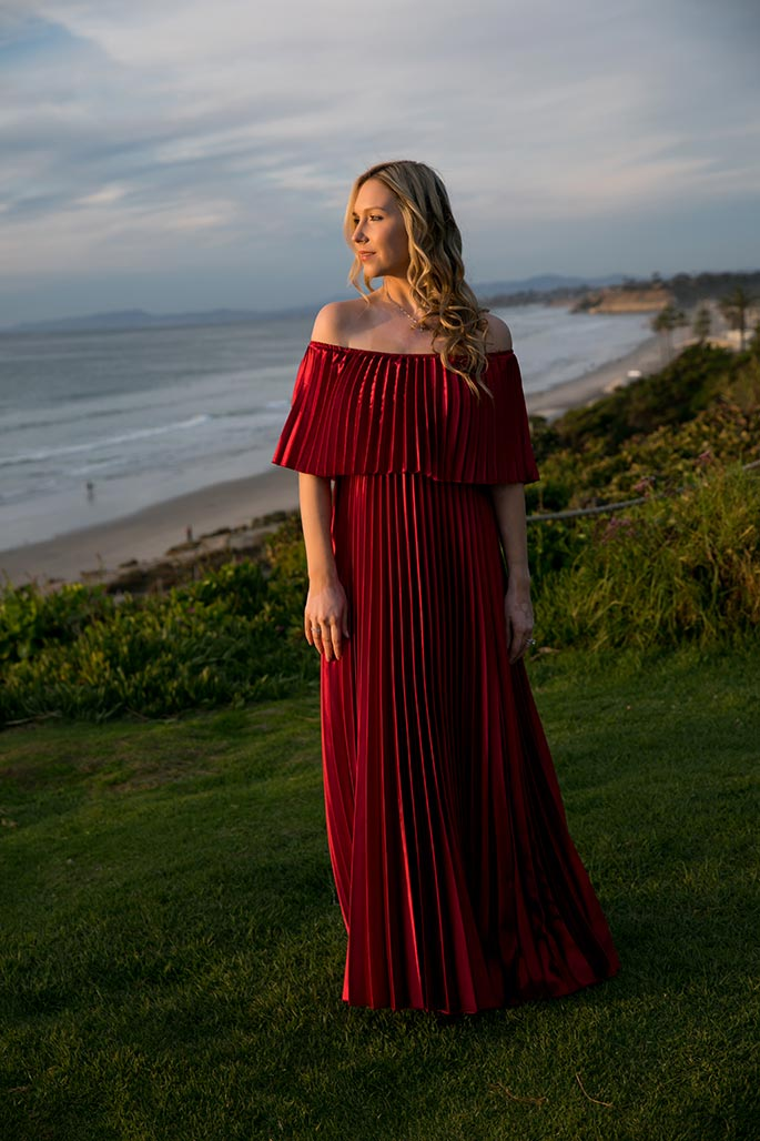 Fashion blogger, Christina Chitwood, looking out at the ocean in metallic red maxi dress. Womens Fashion Amazon Maxi Dress, Circus by Sam Edleman Booties, Nadri Earrings