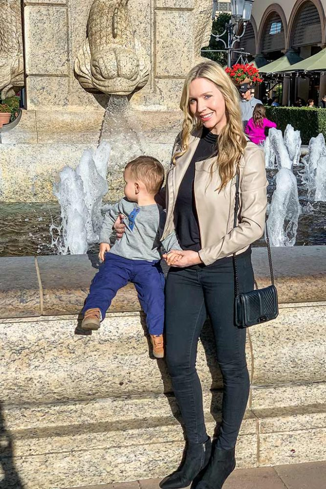 Christina Chitwood with her toddler son in front of a fountain in Newport Beach! She's wearing a Blank NYC Moto jacket, Michael Lauren top, AE jeans, Rebecca Minkoff handbag, and Sam Edelman booties