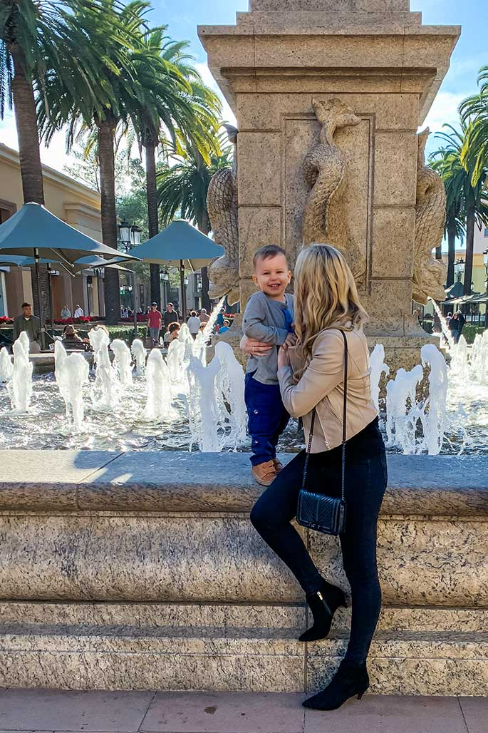 Christina Chitwood with her toddler son smiling in front of a fountain. She's wearing a Blank NYC Moto jacket, Michael Lauren top, AE jeans, Rebecca Minkoff handbag, and Sam Edelman booties