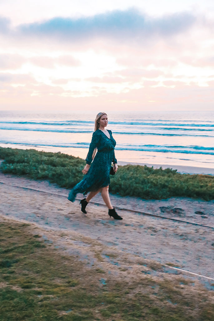 Fashin Blogger, Christina Chitwood, Walking on a Sandy Path in Front of Del Mar Beach. She's Wearing a 1.State Dress, Circus by Sam Edelman Booties, and Rebecca Minkoff Handbag