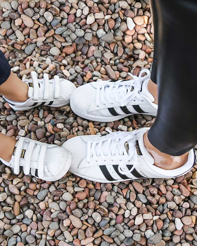 Mom and Toddler Son Wearing Matching Women's and Toddler Boy's Adidas Superstar Sneakers