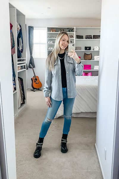 Fashion blogger, Chrissy Chitwood, wearing a grey skirt jacket, shacket, black sweater, distressed skinny jeans, and black combat boots